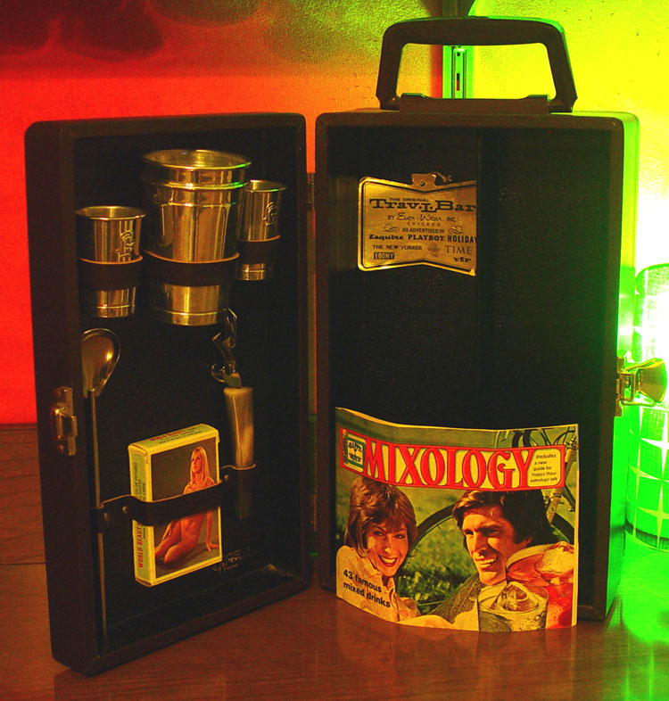 "The idea of ""Booze Luggage"", ""Hooch Suitcases"", ""Portable Pubs"", whatever you choose to call 'em, is largely gone - but these things were crazy popular a few decades ago. I run across them fairly often in the thrifts, and always pick them up if they are in good condition with all of the furniture intact. For $4.99 this one was missing it's deck of cards (middle slot), so I substituted a thematically-appropriate deck from my collection of vintage nudie-cuties."