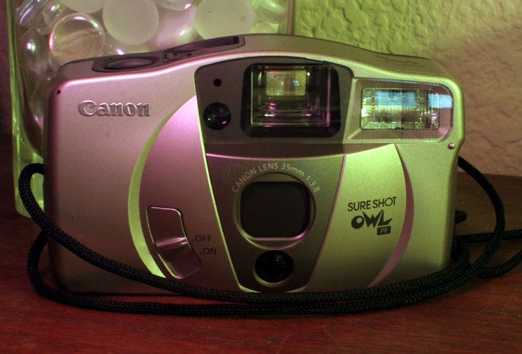 Canon SureShot OWL PF, a pairly normal focus-free P&S with a nice huge viewfinder and (according to the Canon docs) a more powerful-than-normal flash. Takes 2 AA batteries and 35mm film. I've read that hunters liked these a lot because they're easily jury-rigged for a remote tripwire shutter. They apparently used them to scout hunting trails for game.