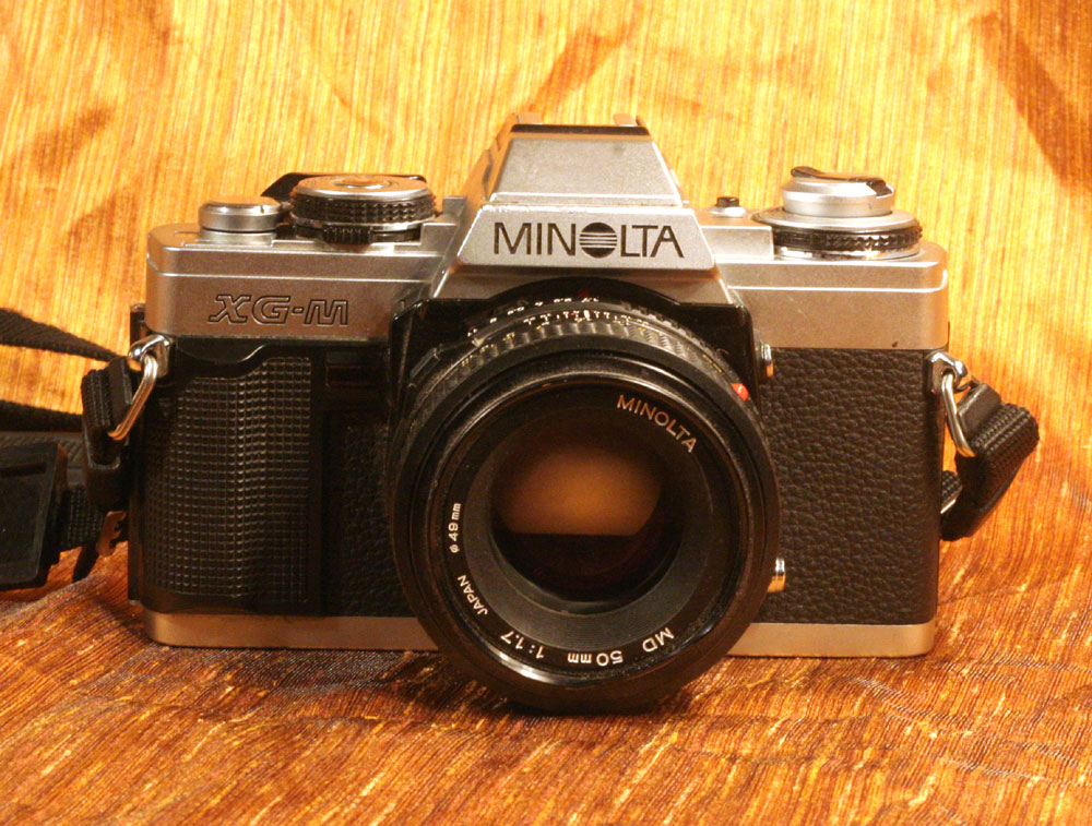 My Minolta XG-M, picked up yesterday at South Goodwill for a pittance, probably because it was seized solid - none of the controls worked, and the shutter was frozen at half-cock. I liked the f1.7 50mm lens and kinda wanted a project to work on this weekend, so I took it home. Turned out all it needed was a fresh battery and a little careful prodding of the shutter. It un-seized with a polite *click* and works great now. :D